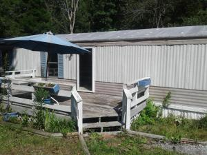 Single wide mobile home sits on great lot.privacy. yard fenced on three sides. Great starter home, or beautiful lot to build on. Lots of potential.