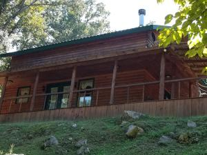 Beautiful custom built cabin in private setting with over  acres of land and a creek. Solid wood doors and trim, spacious country kitchen with custom cabinets, solid wood floors cut from timber on the property, Berber carpet, high end faucets, and a wrap around covered front porch to relax on. This is truly a great find for someone looking for country living.