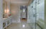 Onxy floor tile, dual vanity sinks, fireplace, crystal chandelier and huge bay window with garden views
