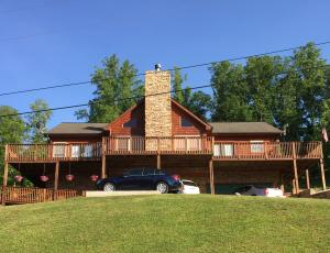 229 Red Oak Circle Carryville, TN. This home is a must see! This home features beautiful hardwoods, a large finished walk out basement, stone fireplace, cathedral ceiling, large wrap around deck, and more! Schedule your showing today