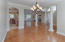 View standing in columned formal dining room out to open family room & Kithen