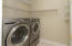 Main level laundry, ceramic tiled floor & plenty of hanging space & additional storage