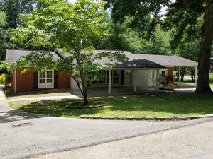 Sprawling Basement Rancher with huge porch in the front and attached carport/workshop.