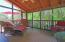 Inviting screened porch overlooks mature backyard