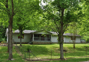 Centrally located convenient to downtown Sevierville, Pigeon Forge and Dollywood, this one level home is situated on 5 private acres and is two homes for the price of one. The main home features an open floor plan, a large living room, gorgeous brand new flooring and a spacious kitchen w/arctic white cabinets and stainless steel appliances including a double oven. A covered front porch is rocking chair ready and plenty of storage for vehicles with a 2-car attached garage and a detached garage. An attached apartment provides individual space for a loved one or potential additional income. The apartment features a fully equipped kitchen, hardwood floors, living room and 2 additional sleeping quarters along with its own driveway and parking. Acreage may be suitable for additional development.