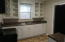 Kitchen features glass door cabinetry and ample room for meal prep