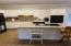 Well laid out island kitchen area with granite countertops and built in bar.