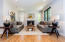 Light flooded keeping room graciously holds seating for 8 around a beautiful gas remote fireplace