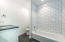 Bedroom 3's en suite features black limestone floors in a popular hex tile and a subway tile tub/ shower