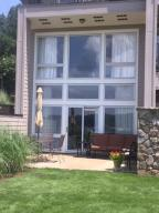Wall of glass lakeside for master on top floor, den on main. Huge patio leads to grassy common area