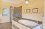 You can't miss the elevated jetted tub, the glass shower, the beautiful tile work and double vanity.