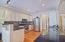 This open concept kitchen features a stainless gas stove, French-style Samsung fridge, double ovens, & a digital microwave