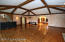 Large family room with vaulted beamed ceilings, gleaming hardwood floors and a traditional bar.