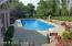 In ground pool is surrounded with a concrete patio, custom hardscaping, and black metal fencing.
