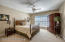 The first additional bedroom offers a double window, neutral carpet and a ceiling fan