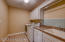 Second floor laundry room features a utility sink, cabinetry and storage for hanging items