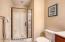 En suite full bath features tile flooring and a walk-in shower with glass door