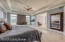 The master suite is well lit with floor to ceiling windows, recessed lighting and overhead ceiling fan fixture