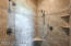 Walk-in shower features glass door, custom tile detail and dual shower heads
