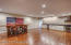 """The walkout lower level features several multi-use spaces including a workout room that can easily be converted into an additional bedroom, and a """"man cave"""" workshop space that features 12'x12' high impact garage tile flooring and is plumbed for a wet bar and utility sink"""