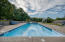 Massive in-ground pool complete with a slide is the perfect spot to cool off on a hot Summer day