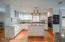 The kitchen boasts stunning granite counters, hardwood floors, a spacious island with electric cooktop, and an abundance of beautiful white cabinetry