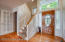 The lovely wainscoting stairwell leads to the second level of the home