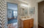 The jack and jill bathroom hosts a tub/shower combination, separate private toilet, vanity with large mirror and lovely sconce lighting