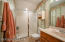 The full guest bathroom features tile flooring and a walk-in shower with glass door
