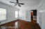 First bedroom features hardwood floors and a ceiling fan