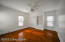 The primary bedroom is well lit with large windows and overhead light fixture with fan