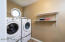 The laundry room is spacious and can be shut off behind a door to hide the mess.