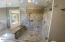 Shower features two shower heads, a large bench and easy access in and out
