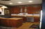 Cheery cabinetry, penisula, stainless appliances in kitchen