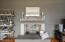 A 2nd wood burning fireplace accented by a brick wall and complete with a custom wood mantle made from reclaimed floor joist beams from the Jim Beam distillery graces the family room