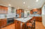 The kitchen features stunning quartzite counter tops, hardwood floors, a spacious island with bar seating for 4 and an abundance of beautiful custom Richelieu cabinetry with undermount task lighting