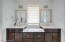 Quartzite countertops, 2 sinks, a make-up vanity, custom lighting, custom mirrors and a window are all features of this bathroom