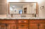 A West Elm mirror and mason jar style light fixtures hang above the double vanities