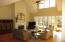 Living area with vaulted ceilings wood floors and gorgeous views out the back.