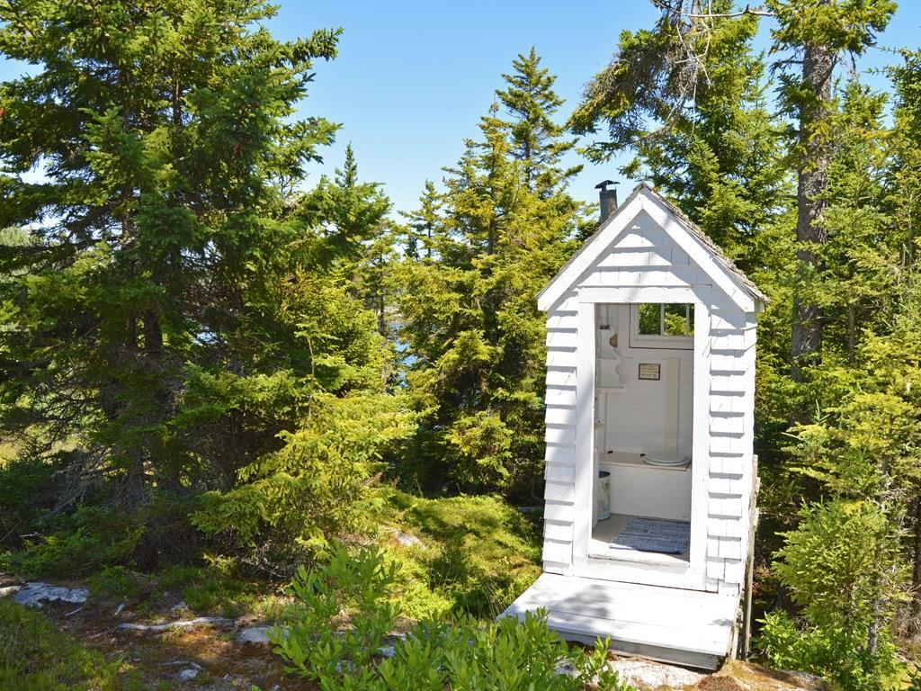 The charming, original outhouse is...