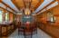 Dining room with stone fireplace and furniture quality built-ins, painted frieze, one of a kind hanging light fixture and extraordinary fir paneled cove ceiling.