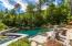 Pool with waterfall and hot tub. Large patio with access to outside shower and changing area.