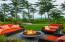 A heated stone terrace with built-in barbecue, sink, refrigerator, fire pit and water feature creates a tranquil outdoor ambiance.