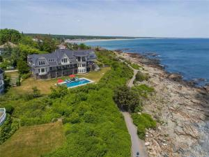 """Juniper Rock"", a New England shingle style residence built in 2014 is located at the ocean's edge in Ogunquit, Maine. The 1.29 acre lot juts out over the famed Marginal Way footpath offering panoramic views of crashing surf, beaches and lighthouses."