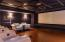 The lower level theater sports eleven leather reclining chairs, 140 inch viewing screen and midnight blue swede paneled walls.