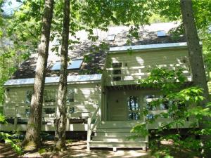 Large waterfront home on Moose Pond great for entertaining - summer or winter! This side of the house faces the water. Very private back deck with hot tub.