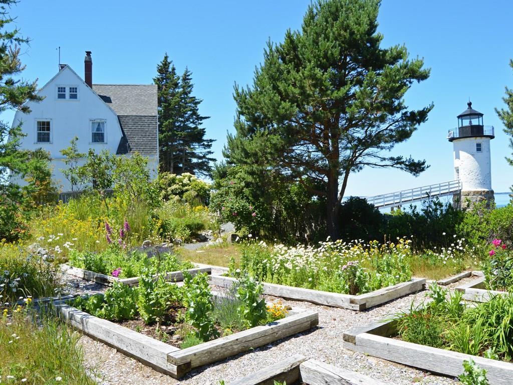Perennial flower gardens frame a...