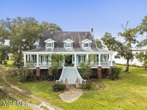 Unique properties like this raised Southern home rarely come on the market! It boasts gracious porches tucked beneath a deep overhang where you can feel the silky breezes from the Gulf. If you want privacy and seclusion, but still relatively close to everything! This property has gorgeous trees with Spanish hanging moss and an unparalleled view.