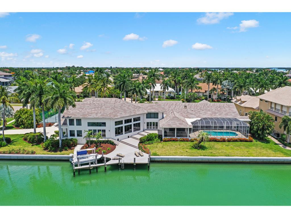 Stunning home located in the estate ares of Marco Island, offers Island living at its finest. This rare 7 bdrm 9 bath home on two lots features direct access to Robert's Bay. Extensive renovations in 2019/2020 through-out including NEW seawall, impact windows, doors, roof, lighting, and landscaping. This home makes entertaining family and friends easy with a living room, family room, billiards table, bar area, flat screen TV, and a dining room that can accommodate 20 guests with two large tables and a round table that can accommodate 6. The kitchen can seat 8 and boasts an electric cook-top, wall oven and SS appliances. The large master suite features a sitting area, two walk-in closets, French doors leading to the lanai and an en-suite bathroom with dual sinks, shower and a separate tub. Each guest bdrm offers their own private bathrooms with walk in showers perfect for privacy. This beautiful home features a large, covered lanai area that overlooks the gorgeous pool and spa. For the tennis or basketball player there is a tennis/basketball court on the property. The back of the home with Western exposure, has a boat dock and lift with direct access water access to Robert's Bay.