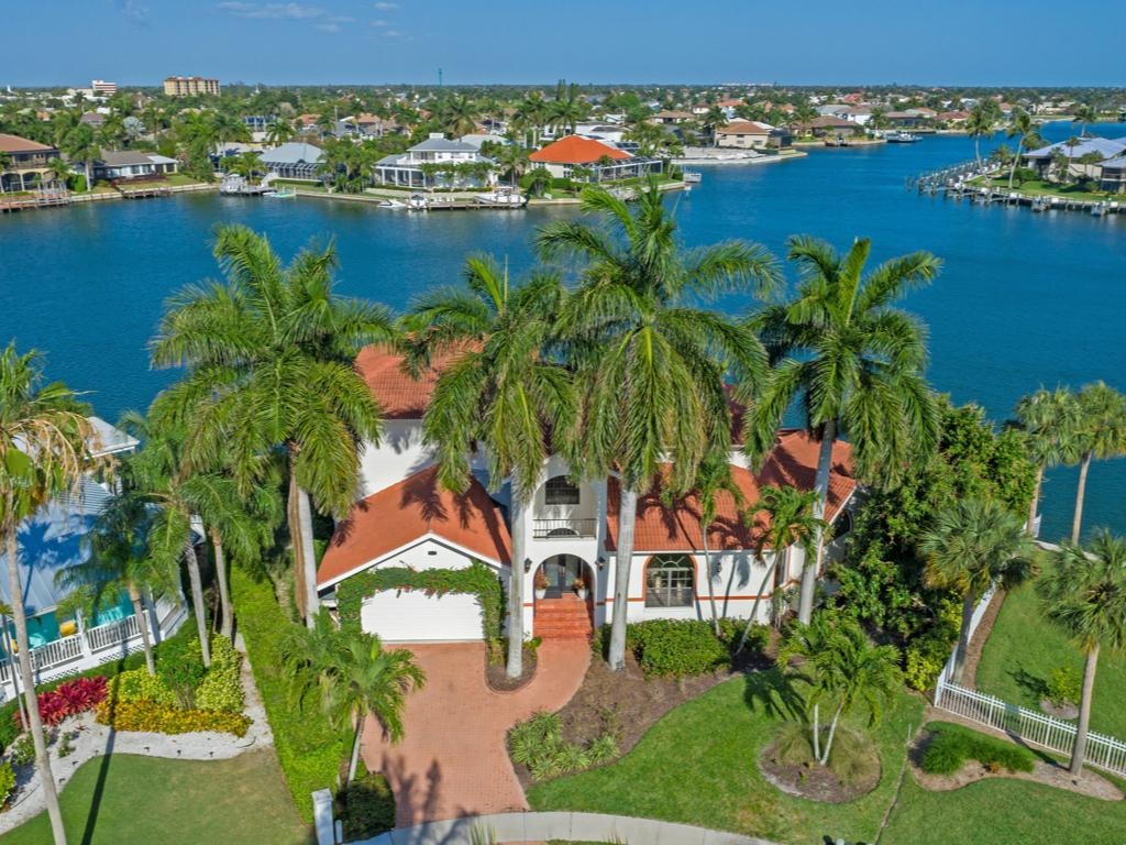 Location, location, location!! Look no further for the very best views of Clam Bay in the popular Tigertail Beach neighborhood. This custom 2-story residence is in an exquisite neighborhood & is super close to a beach entrance. Sets of French doors at the grand living room open to the outdoor living area, pool & amazing waterfront. The master bedroom suite is on the first floors where unbelievable sunrises will be enjoyed. The lovely winding staircase leads up to a sitting area, the guest quarters and a screened balcony. Each bedroom suite was purposefully designed to capture views along the gorgeous waterfront, adding more bright light & cheerfulness to this home! This is a tip lot, so the dock is off to the side leaving unobstructed bay views & loads of privacy. Perfect water indirect location here with easy access to the Gulf by boat & sunny SE exposure on the pool deck. There are newer pavers at the pool & a newer roof. Outdoors you'll enjoy no unsightly power lines as all utilities are underground, a rare feature at Marco Island. Outstanding opportunity!